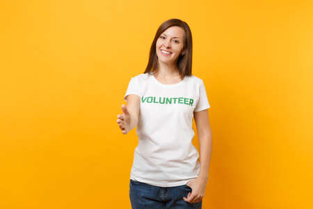 Foto de Portrait of happy smiling satisfied woman in white t-shirt with written inscription green title volunteer isolated on yellow background. Voluntary free assistance help, charity grace work concept - Imagen libre de derechos