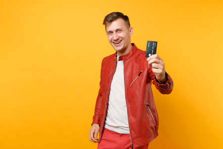Foto de Portrait vogue smiling handsome young man in red leather jacket t-shirt hold bank credit card isolated on trending yellow background. People sincere emotions lifestyle concept. Advertising area - Imagen libre de derechos