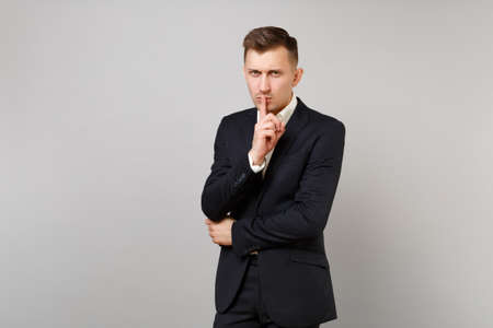 Foto de Serious young business man in classic black suit shirt say hush be quiet with finger on lips, shhh gesture isolated on grey background. Achievement career wealth business concept. Mock up copy space - Imagen libre de derechos