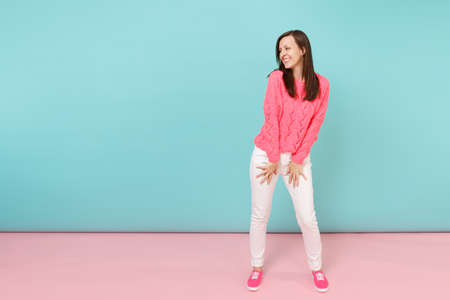 Photo for Full length portrait of smiling young woman in knitted rose sweater, white pants posing isolated on bright pink blue pastel wall background in studio. Fashion lifestyle concept. Mock up copy space - Royalty Free Image