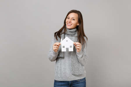Photo pour Smiling young woman in gray sweater, scarf holding paper white house isolated on grey background in studio. Healthy fashion lifestyle, people sincere emotions, cold season concept. Mock up copy space - image libre de droit