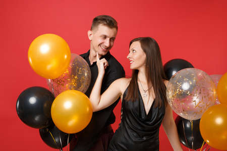 Photo for Stunning young couple in black clothes celebrating birthday holiday party isolated on bright red background air balloons. St. Valentine's International Women's Day Happy New Year 2019 concept. - Royalty Free Image