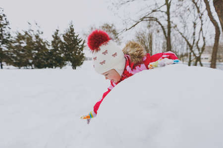 Foto de Smiling little girl in winter warm clothes and hat playing and making snowball in snowy park or forest outdoors. Winter fun, leisure on holidays. Love relationship family childhood lifestyle concept - Imagen libre de derechos