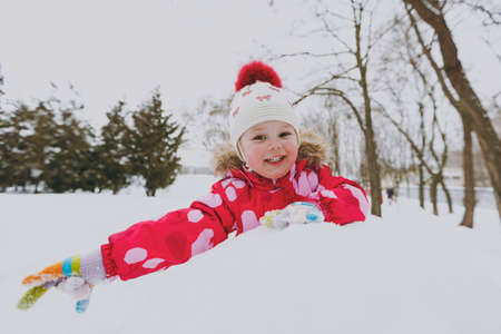 Foto de Happy little girl in winter warm clothes and hat playing and making snowball in snowy park or forest outdoors. Winter fun, leisure on holidays. Love relationship family childhood lifestyle concept - Imagen libre de derechos