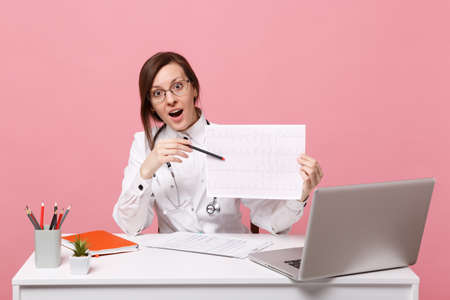 Foto de Female doctor sits at desk works on computer with medical document heart ekg in hospital isolated on pastel pink wall background. Woman in medical gown stethoscope. Healthcare medicine concept - Imagen libre de derechos