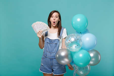 Foto de Amazed young woman holding fan of money in dollar banknotes cash money, celebrating with colorful air balloons isolated on blue turquoise background. Birthday holiday party, people emotions concept - Imagen libre de derechos