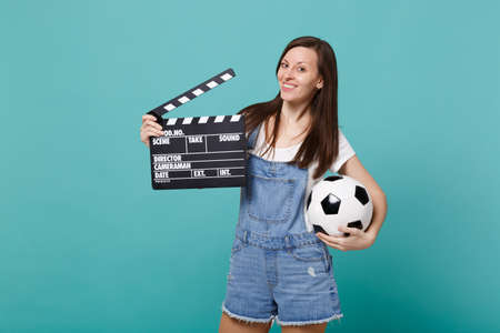Foto de Beautiful young woman football fan support favorite team with soccer ball, classic black film making clapperboard isolated on blue turquoise background. People emotions, sport family leisure concept - Imagen libre de derechos