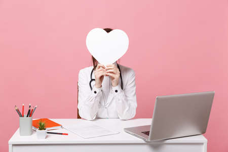 Foto de Female doctor sit at desk work on computer with medical document hold heart in hospital isolated on pastel pink wall background. Woman in medical gown glasses stethoscope. Healthcare medicine concept - Imagen libre de derechos