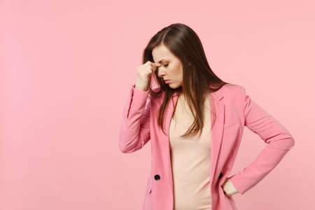 Photo for Portrait of tired upset young woman wearing jacket putting hand on nose, keeping eyes closed isolated on pastel pink wall background. People sincere emotions, lifestyle concept. Mock up copy space - Royalty Free Image