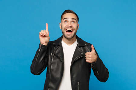 Photo pour Stylish young bearded man in black leather jacket white t-shirt holding index finger up with great new idea isolated on blue background. People sincere emotions lifestyle concept. Mock up copy space - image libre de droit