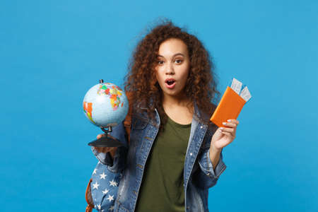 Foto de Young african american girl teen student in denim clothes, backpack hold pass isolated on blue wall background studio portrait. Education in high school university college concept. Mock up copy space - Imagen libre de derechos