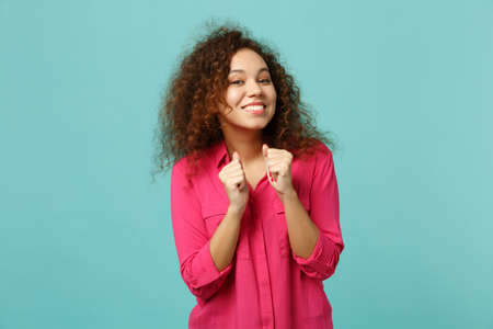 Foto de Portrait of smiling pretty african girl in pink casual clothes clenching fists isolated on blue turquoise wall background in studio. People sincere emotions, lifestyle concept. Mock up copy space - Imagen libre de derechos