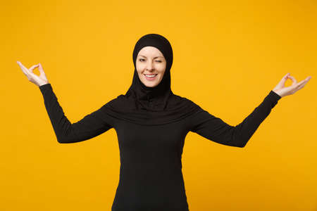 Foto de Young arabian muslim woman in hijab black clothes hold hands in yoga gesture, relax meditating isolated on yellow background, studio portrait. People religious lifestyle concept. Mock up copy space - Imagen libre de derechos