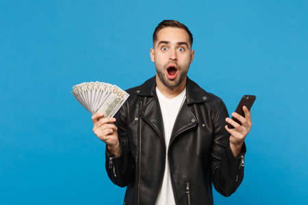 Photo pour Young man in black leather jacket white t-shirt holding fan of cash money in dollar banknotes, cellphone isolated on blue wall background studio portrait. People lifestyle concept. Mock up copy space - image libre de droit