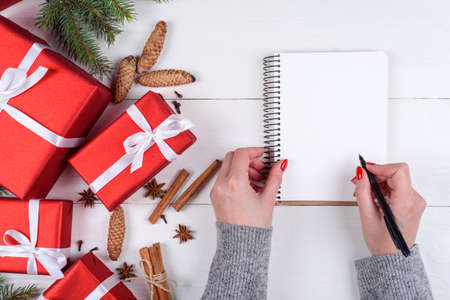 Photo pour Top view of Christmas background with blank empty diary and girl's hands with pen writing goals on white wooden background, free space. Flat lay, top view - image libre de droit
