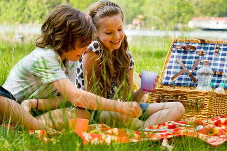 Photo pour Two children enjoying a picnic in the summer - image libre de droit