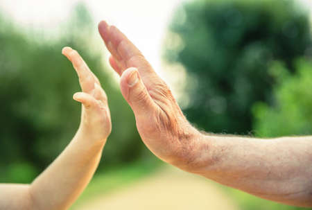 Child and senior man hands giving five over a nature background. Two different generations concept.