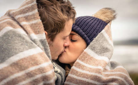 Photo for Closeup of young beautiful couple kissing under blanket in a cold day with sea and dark cloudy sky on the background - Royalty Free Image
