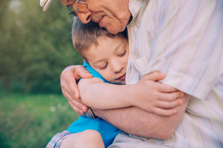 Photo for Portrait of happy grandson hugging grandfather over a nature outdoor background. Two different generations concept. - Royalty Free Image