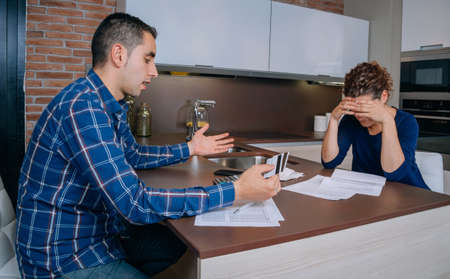 Desperate and unemployed young couple reviewing their credit card debts. Financial family problems concept.