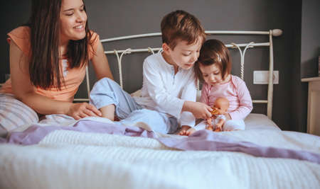 Portrait of happy children feeding doll with a cookie sitting in the bed with their mother in a relaxed morning.