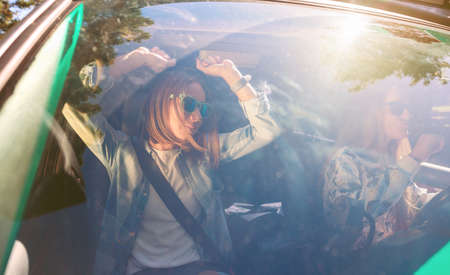 Photo pour Two happy young women friends with sunglasses dancing and having fun inside of car in a road trip adventure. Female friendship and leisure time concept. - image libre de droit