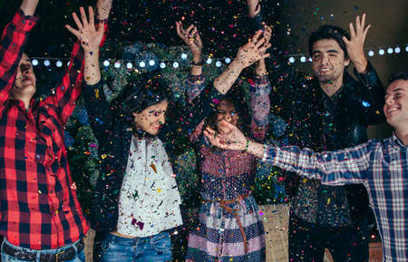 Closeup of happy young friends raising their arms and having fun among the colorful confetti cloud in a outdoors party. Friendship and celebrations concept.