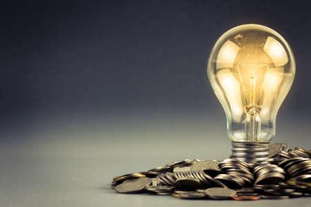 Foto de Light bulb and pile of coins with copy space - Imagen libre de derechos