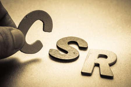Foto de Closeup finger picking a small English letter to put in the CSR (Corporate social responsibility)  abbreviation - Imagen libre de derechos
