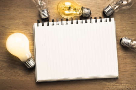 Photo for Spiral notebook with light bulbs on wood background - Royalty Free Image