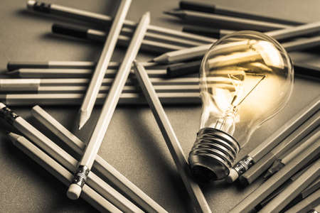 Photo pour Creative writing, light bulb and many pencils on the table - image libre de droit