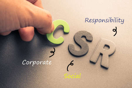 Foto per Closeup hand arrange wood letters as CSR abbreviation(Corporate social responsibility) - Immagine Royalty Free