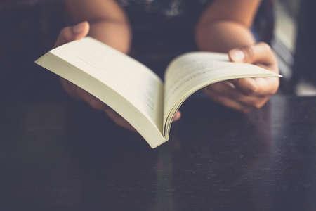Foto de Woman place her arms on her lap and open book to read - Imagen libre de derechos
