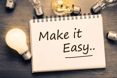 Foto de Make It Easy concept, handwriting on notebook with light bulbs - Imagen libre de derechos