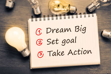 Foto de Dream Big - Set Goal - Take Action, handwriting on notebook with light bulbs - Imagen libre de derechos