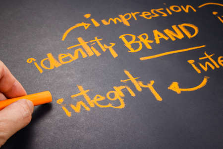 Foto de Hand writing Brand concept on chalkboard, focus at Integrity word - Imagen libre de derechos