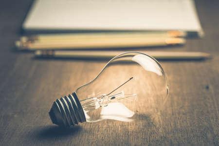 Photo pour Light bulb with pencils and notebook on background - image libre de droit