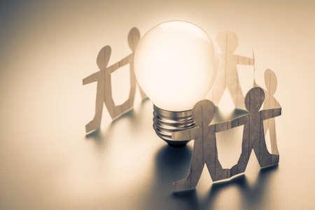 Foto de Human chain paper with glowing light bulb - Imagen libre de derechos