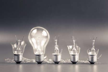 Photo pour Perfect light bulb glowing in a row of broken bulb for solution concept - image libre de droit