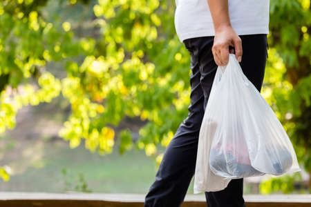 Photo for Closeup woman carry the grocery plastic bags while walking in the forest park, environment concept - Royalty Free Image