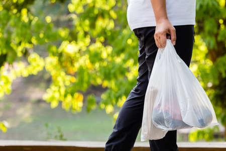 Foto de Closeup woman carry the grocery plastic bags while walking in the forest park, environment concept - Imagen libre de derechos