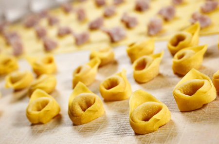 Photo pour Tortellini. Italian homemade stuffed pasta made with fresh pasta kneaded with flour and eggs; stuffed with meat and parmesan cheese. - image libre de droit