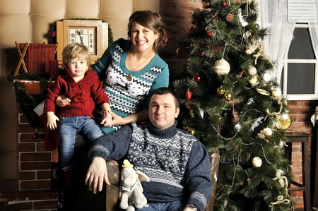 Portrait of a friendly family with pregnant woman during Christmas time