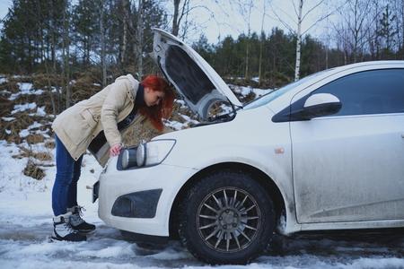 Foto de Young redhead girl looks under cowl of broken car on rural road - Imagen libre de derechos