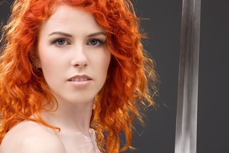 lovely redhead with medieval sword over grey