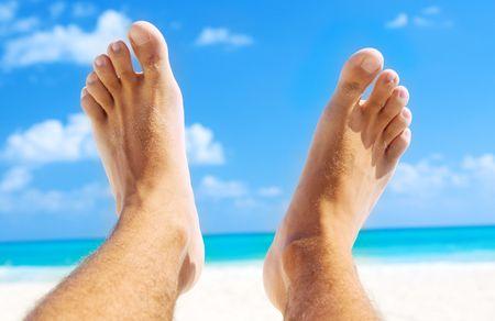 Foto de picture of male legs over tropical beach background - Imagen libre de derechos