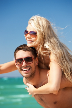 picture of happy couple in sunglasses on the beach  focus on man