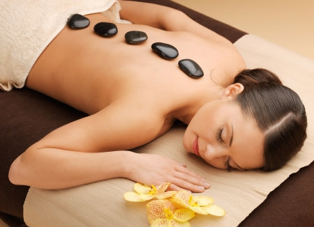 Photo for picture of woman in spa salon with hot stones - Royalty Free Image