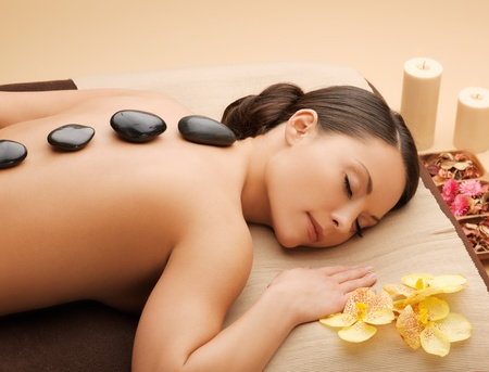 picture of woman in spa salon with hot stones