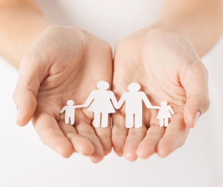 Photo pour close up of womans cupped hands showing paper man family - image libre de droit